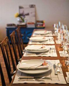Sobre a mesa, quase tudo é alugado – um jeito prático e econômico de variar a produção a cada jantar. Jogos americanos e guardanapos de linho com ponto ajour são da Ritz Festas, assim como os talheres de prata, os pratos brancos e os copos de vinho.
