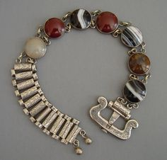 "Scottish silver and agate buckle bracelet, small agate circles in different colors and designs with buckle decorated with scrolls and leaves, each tubular link etched design total length 9-1/2"", wearable length 6-1/2"" to 8"" by 1-1/8"" wide buckle and 5/8"" circles, circa 1880. Bracelets similar to this can be seen in ""Scottish Jewellery A Victorian Passion"" by Diana Scarisbrick on page 74."