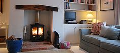 Wood burning stove on brick plinth and hearth with chunky wood mantelpiece