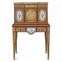 A FRENCH GILT-BRONZE-AND PORCELAIN-MOUNTED EBONY INLAID KINGWOOD, TULIPWOOD AND PARQUETRY BONHEUR DU JOUR IN LOUIS XVI STYLE, CIRCA 1870 in the manner of Martin Carlin,  the Spanish portor moulded marble top above a frieze applied with vine leaves, the central door mounted with a gilt-bronze plaque showing Venus at her toilet between doors applied with Sèvres  'bleu celeste'  style plaques, each small cupboard fitted with drawers, the lower section with conforming decoration and a fitted ...
