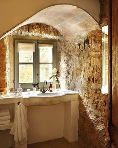 Rustic bathroom. Love the walls. The window frame colour and latch. The cement vanity is simple but goes with the whole room.