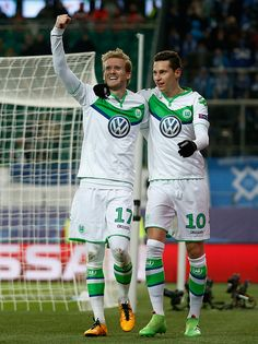 Andre Schuerrle of Wolfsburg celebrates with Julian Draxler after scoring his team's first goal during the UEFA Champions League round of 16 second...