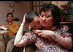 """In this May 1997 file photo, Phan Thi Kim Phuc holds her son Thomas, in their apartment in Toronto. Her husband, Bui Huy Toan is to the left. The """"napalm girl"""" now.after defecting to Canada.and reading the Bible. Napalm Girl, Revision Techniques, Turning 40, Thing 1, Iconic Photos, Jackie Chan, Interesting History, Vietnam War, Girl Photos"""