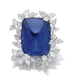 Impressive sapphire and diamond brooch. ~ The cabochon sapphire is of Burmese origin, with no indications of heating are set within a frame of pear- and marquise-shaped diamonds.