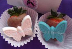 Fresas con chocolate decoradas con una mariposa de chocolate blanco y azul.