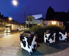 Feed the Cows  Artmongers, 2005. New Cross Road, Commissioned by NDC. Designed to promote recycling in the borough and to turn the humble dustbin into a work of art, these Friesian cow bins have now been commissioned by other boroughs.