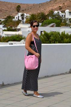 Look con vestido de lunares y bolso rosa.