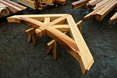 Fully assembled timber frame truss with curved bottom chord.