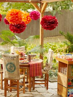 Add warmth to a small patio with an array of textures: rustic stone, burlap covered chairs and tissue paper pom-poms.