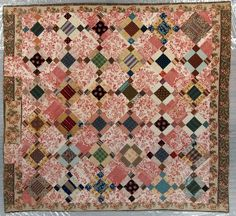 "Pieced Quilt, ca. 1820, Nine Patch Variation. Thirty-two 8 1/2"" tan, rust, brown and blue patch blocks set diagonally on point alternate with the same sized red and white printed chintz blocks ."