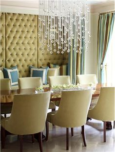 Dining Room by Tobi Fairley. The tufted wall, a bold gesture in this dramatic dining room, works beautifully against the clean lines of the dining table and chairs. The window treatments, while lush in their own right, frame the wall rather than compete with it. The crystal chandelier offers a contemporary twist on Hollywood-era glamour.