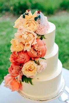 A three-tiered white wedding cake with flowers | @jessepafundi | Brides.com