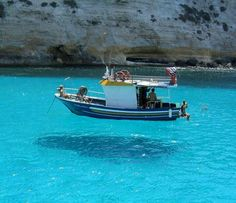 The water is so clear it looks like the boat is floating on air! Greece!
