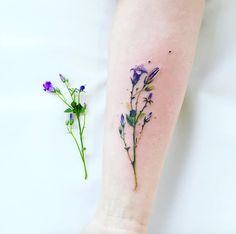 Hyper-realistic wildflower tattoo by Pis Saro