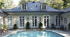 Stucco French Pavilion style. French country pool pavilion, light stucco with heavy white trimmed windows and dormers.