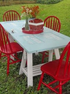 Turn an old door into a picnic table!! LOVE the red chairs!