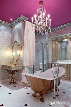 Very formal bathroom with hot pink ceiling and silver and white wallpaper.... a golden tub and a formal chandelier of glass and crystal...Bebe' !!!