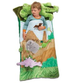 """jurassic dreams sleeping bag - the most awesome sleeping bag that ever inhabited the earth. it's an eye-popping feast for young dino fans. the shell's a landscape of scrumptiously plush designs, with 4 soft toy-species that attach with Velcro. plus that large green dinosaur which is, yes, a plush pillow! Fleece lined. 52"""" x 28""""."""