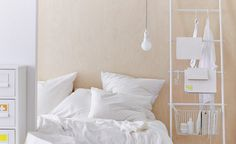 A white towel holder, designed as a ladder, with a basket leaned against a wall beside a bed.
