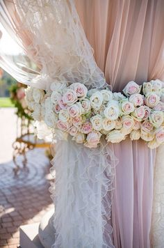 Sheer pink linens and ruffled white curtains are bound by beautiful fresh rose wreaths.