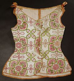 "1730s British Woman's waistcoat at the Glasgow Museums, Glasgow - From the curators' comments: ""This informal lady's waistcoat would have been worn informally with a quilted petticoat and gown, or underneath a dress as additional layer for warmth...[Many] are made using un-dyed linen quilted using a cream or light yellow thread. This item is more flamboyantly decorated with medallions, Staffordshire knots and quatrefoils worked in silk and wool threads."""