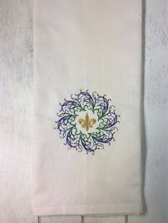 The ecru colored dish towel has been beautifully accented with a filigree wreath of purple, green, and gold. The wreath design is a airy and light design and can be personalized to match your decor. The gold fleur de lis is centered within the wreath to complete this Mardi Gras themed dish towel. This towel is very versatile as it can be used in your guest bathroom as a hand towel or in your kitchen for a dish towel. The towel is made of 100% cotton and measures approximately 16 inches by 28…