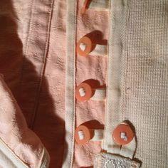 Praktikus, hogy a gombok pamut textil szalagra vannak fűzve. Jobb és bal oldalon illetve középen gumiszállal szőtt pamut betét biztosítja a komfortosan elasztikus (strech) viseletet.- girdle 1910 körül  http://reviania.blogspot.hu/2017/01/girdle-ez-talan-tobb-mint-vintage-akar.html