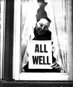 1940: A woman putting an 'All Well' sign in her window during the Blitz. (Photo by London Express/Getty Images)