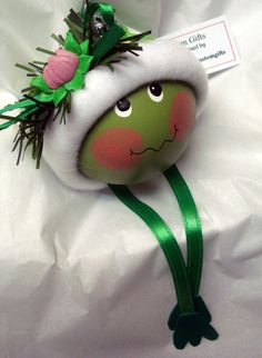 This hand painted frog face ornament is wearing a handmade fleece trimmed green ladybug print hat with a lily pad and a green ribbon on top. Frog Ornaments, Christmas Ornament Crafts, Hand Painted Ornaments, Christmas Crafts For Kids, Christmas Balls, Christmas Art, Christmas Projects, Holiday Crafts, Handmade Ornaments