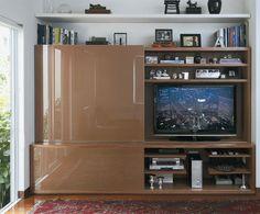 """Feito de timburana com portas de vidro pintado, o móvel do home theater foi executado pela Marcenaria Di Legno. Pintada de branco, a prateleira acima dele exibe objetos de decoração. """"É uma solução que dá leveza ao conjunto"""", explica Tania."""