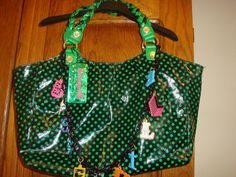 """Great tote gets its charm from the polka dots and the chain link with dangling charms that spell BETSEYVILLE. Hanging """"BETSEYVILLE luggage tag"""" The signature XOX BETSEY Hot Pink lips with embedded rhinestone are on one side."""