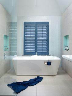 Beautiful blue shutters in a contemporary bathroom design. http://www.theshutterstore.com