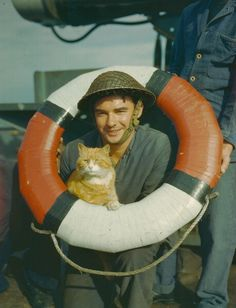 1944 - A US Marine posing with Sandy the cat, acting mascot of a Sea Fort in the Thames Estuary during World War Two, October 1944. (Photo by Popperfoto/Getty Images)
