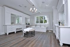 This spacious master bathroom has two large vanities and a soaking tub making this space a spa-like retreat. The vaulted ceilings and chandelier give this space a grand feel.