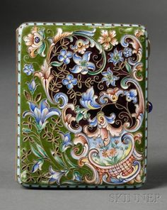 Russian Silver, Cloisonne, and En Plein Enamel Cigarette Case, Moscow, 1908-17, maker's mark S.Zh, rectangular with rounded corners, enameled with cloisonne foliate cartouches with green and maroon ground, the maroon ground above a small C-scroll cartouche enclosing an en plein enamel of wildflowers on a sky blue ground, with blue cabochon stone latch, gold-washed interior - Skinner Auction 10 av 2010.