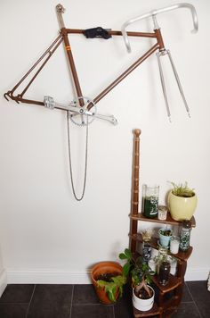 A bike frame hangs on the wall of their sunny bathroom.