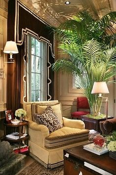 The black window treatment is striking because of the art deco design and the large fern adds drama