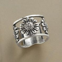 "sunflower ring......                  tournesol ring  Caught between two silver bands, a trio of sculpted sterling sunflowers rings your finger. Exclusive. Whole sizes 5 to 10. 1/2""W."