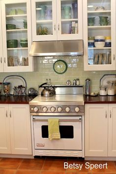 Love everything about this! Off white cabinets, butcher block countertops, green subway tiles