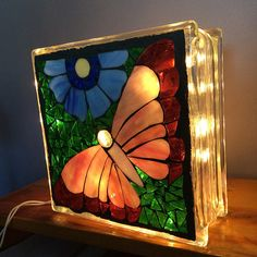 Gorgeous just finished stained glass butterfly mosaic with a blue cosmos flower. The butterfly is pink and purple glass with a white iridescent body and a glass drop for its head on a cathedral green background. This is a one of a kind piece that I designed and made. The brick is