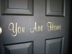 love the inscription on this black door: you are home Black Garage Doors, Black Doors, Parfait, Garage Door Makeover, Garage Entry, Front Door Porch, Thrifty Decor Chick, You Are Home, Inspired Homes