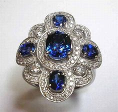 An 18ct white gold sapphire and diamond dress ring, with a central oval cut sapphire having an estimated weight of 1.55ct, and a further four sapphires set amongst 100 pave set brilliant cut diamonds in a foliate design. Estimated total diamond weight: 0.61ct