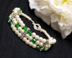 Triple strand, ivory pearl bracelet with jade green beads and rhinestone spacers. Renaissance style toggle clasp. Evening or formal wear