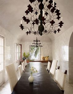 Circa-1800 French chandeliers hang above a slate table in a Riviera villa's tiled dining gallery.