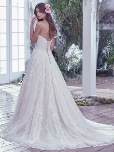 Maggie Sottero - TEMPERANCE, A sweet yet sophisticated tulle ball gown, adorned with embroidered lace, features a strapless fitted bodice, beaded belt with Swarovski crystals, and effortlessly full skirt with a gorgeous lace hemline. Finished with a corset closure.