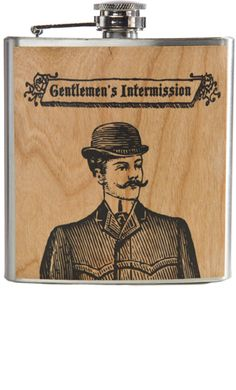 """SPITFIRE GENTLEMENS CLUB FLASK    Price:$25.00    Like any prim and proper gentleman, you should always have your Spitfire flask by your side! This stainless steel flask features a real wood veneer of a dapper young gent printed in black with """"Gentlemen's Intermission"""" above is head. This 6 ounce flask comes in a handy printed muslin bag.  4"""" by 4"""" by 1"""""""