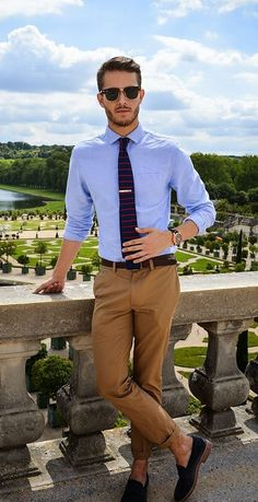 Dark Brown Sunglasses, Light Blue Dress Shirt, Navy Horizontal Striped Tie, Dark Brown Leather Belt, Brown Chinos, Black Suede Loafers and overall he is perfect.
