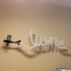 My sons airplane with name trail! Floral wire painted white with pillow stuffing glued on. Hung by fishing wire