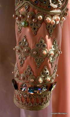 Closeup of a sleeve on a caftan from Caftan 2013 in Marrakech during May 2013. The twisted silk threads are stitched onto the fabric by hand; sometimes pearls, crystals of sequins are added. Real caftans which are made entirely by hand represent a significant outlay in money, costing hundreds (minimum price is around $200) or even thousands of dollars.