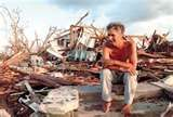 A woman sits by the ruins of her house after it was destroyed by Hurricane Andrew. This picture evokes feelings of confusion and helplessness since the woman is clearly in shock and is unsure what to do next.